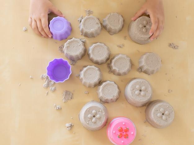 Het mooie meisje spelen met kinetisch zand thuis