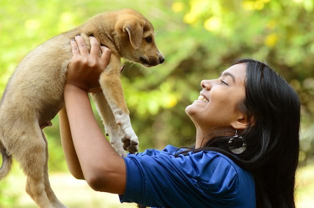 Het mooie meisje spelen met puppyhond in openlucht in park