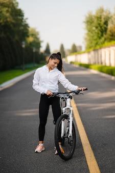 Het mooie meisje stellen bij witte fiets