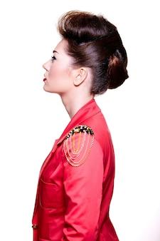 Het mooie meisje stellen op wit die rood jasje dragen