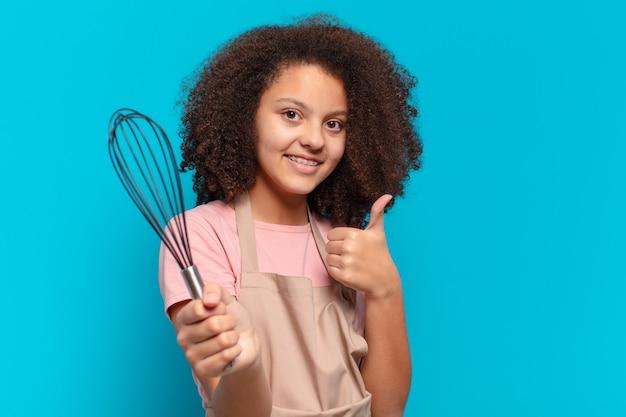 Het mooie meisje van de afrotiener koken met een schort en een mixer. bakker concept
