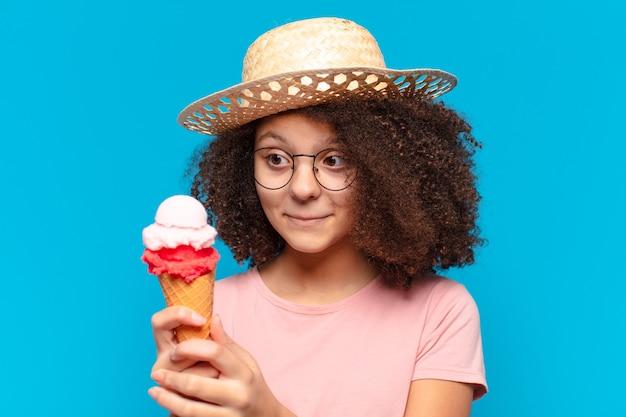 Het mooie meisje van de afrotiener met hoed en het hebben van een roomijs. zomer concept
