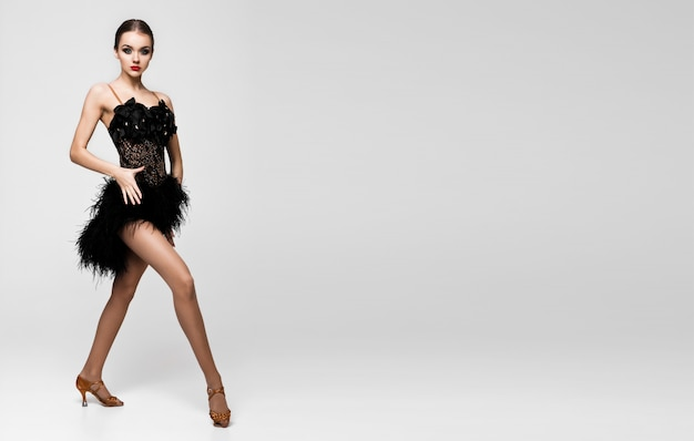 Het mooie meisje van de balzaaldanser in elegant stelt zwarte kleding op grijze achtergrond
