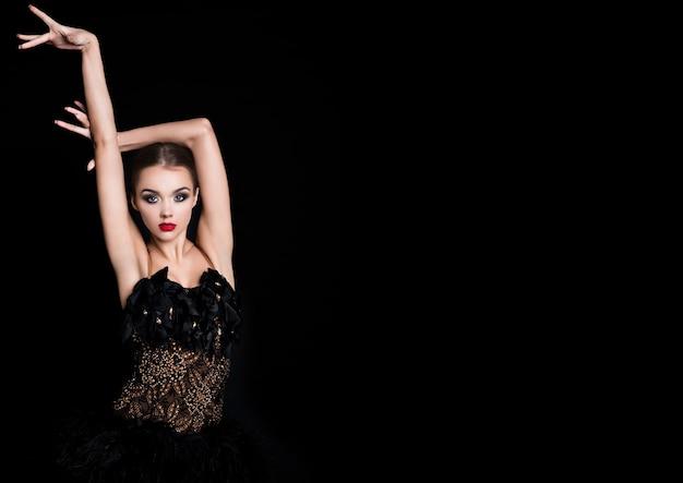 Het mooie meisje van de balzaaldanser in elegant stelt zwarte kleding op zwarte achtergrond