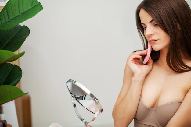 Het mooie meisje veegt het gezicht af na het nemen van een douchespons
