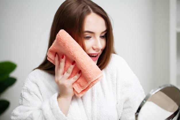 Het mooie meisje veegt thuis haar gezicht met een handdoek voor een spiegel af