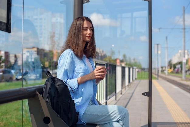 Het mooie meisje wacht op metro of tram op openbaar vervoerpost in de ochtend. gelukkige jonge vrouw met kop van koffie op openbare post.