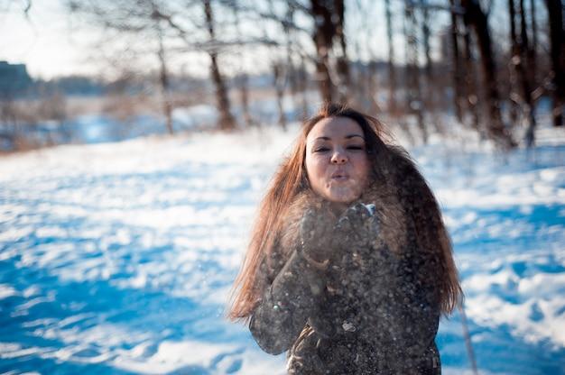 Het mooie meisje werpt sneeuw in het bos
