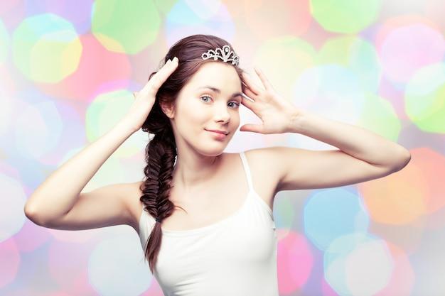 Het mooie meisje zet een diamanten tiara op en bewondert zichzelf