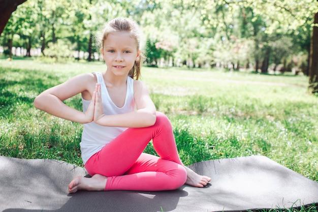 Het mooie meisje zit op carimate in een yogapose. ze heeft haar benen over elkaar geslagen, maar ze houdt haar handen bij elkaar. ze lacht. yoga en pilates concept.