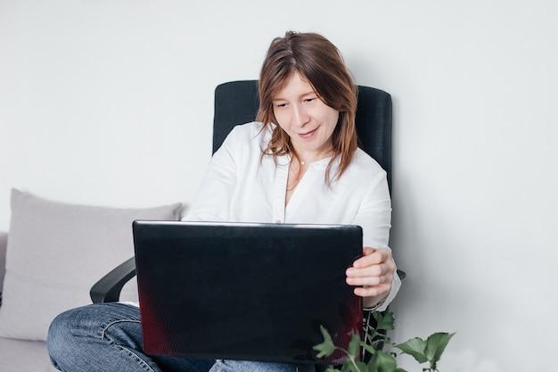 Het mooie meisje zit thuis in een bureaustoel met een laptop in haar handen, met positieve emoties en een mooie glimlach