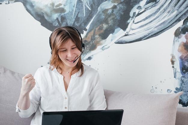 Het mooie meisje zit thuis op de bank met een laptop in haar handen en koptelefoon, met positieve emoties en een mooie glimlach