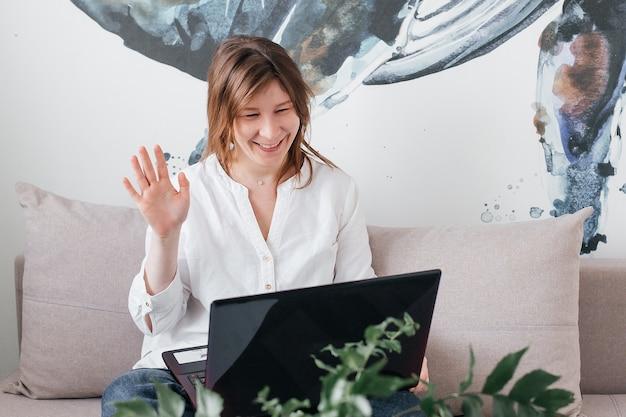 Het mooie meisje zit thuis op de bank met een laptop in haar handen, met positieve emoties en een mooie glimlach