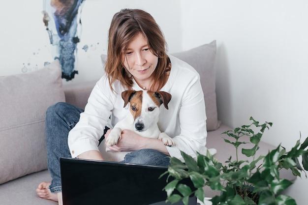 Het mooie meisje zit thuis op de bank met een laptop op tafel, naast een jack russell-hond
