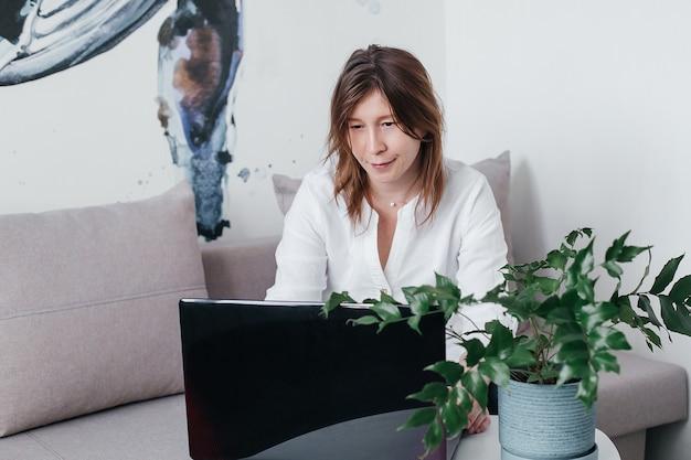 Het mooie meisje zit thuis op de bank met een laptop op tafel