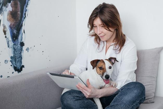 Het mooie meisje zit thuis op de bank met een tablet in haar handen, naast een jack russell-hond