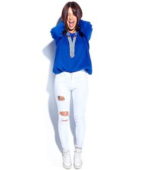 Het mooie model van de hipster donkerbruine vrouw in toevallige modieuze de zomer blauwe sweater die op witte achtergrond wordt geïsoleerd. haar tong tonen, volledige lengte