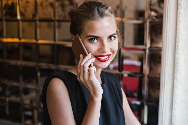 Het mooie model van het close-upportret in cafetaria. ze spreekt aan de telefoon, lacht naar de camera.