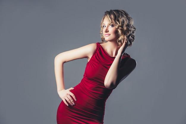 Het mooie model van het vrouwenblonde in rode kleding modieus en elegant in de studio