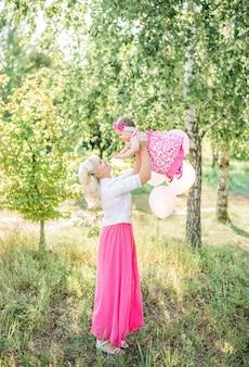 Het mooie moeder spelen met babymeisje in aard in de zomer