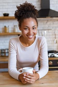 Het mooie mulatmeisje zit bij de lijst met kop van ochtendthee of koffie en het glimlachen bekijkend de camera