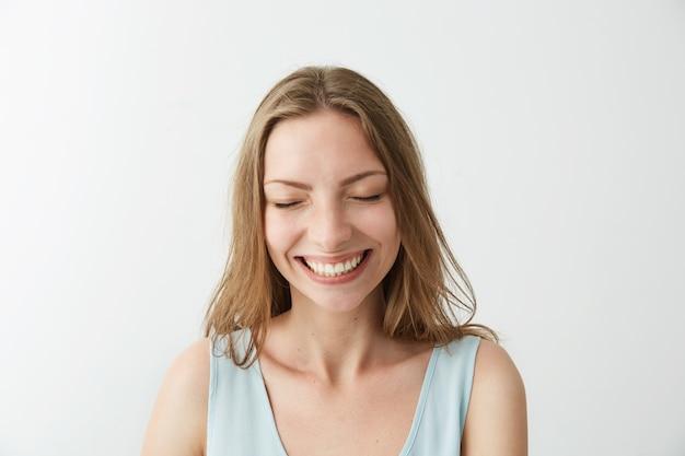 Het mooie oprechte gelukkige vrolijke meisje glimlachen die met gesloten ogen lachen.