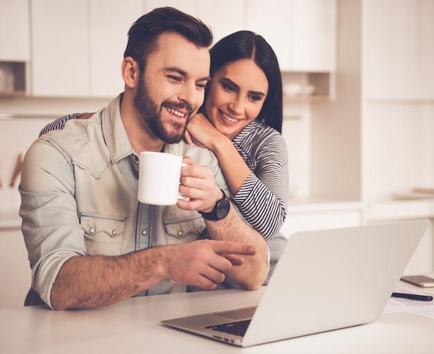 Het mooie paar gebruikt laptop en drinkt koffie