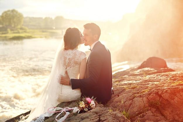 Het mooie paar houdt van kussen terwijl het zitten op rotsen dichtbij rivier