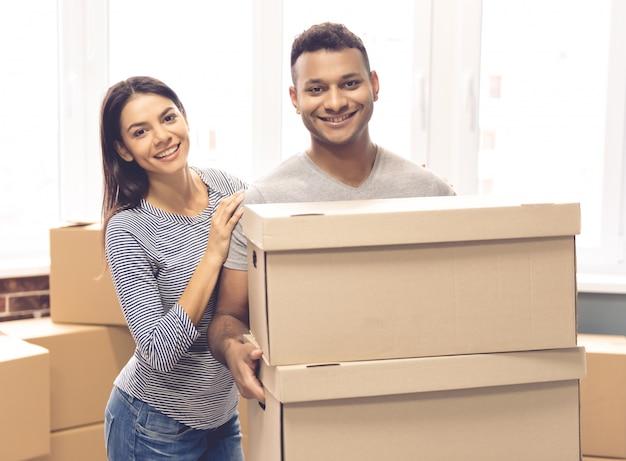 Het mooie paar houdt verhuisdozen.