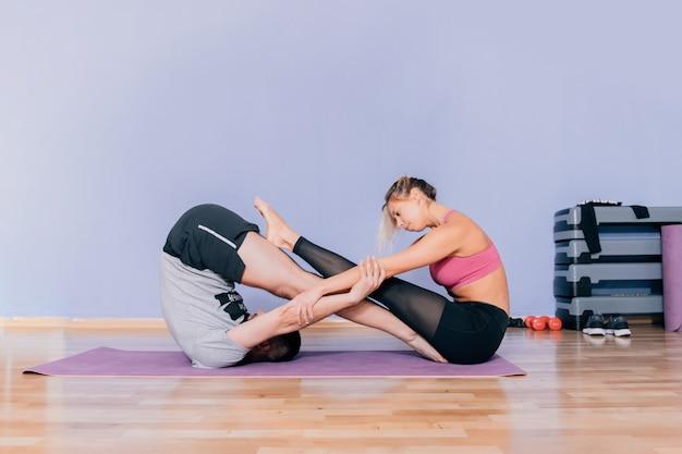 Het mooie paar in sportkleren rekt zich op yogamat uit terwijl thuis het trainen of gymnastiek. oneindige yogapose voor vrienden.