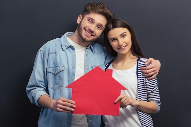 Het mooie paar in vrijetijdskleding houdt een papieren huis.