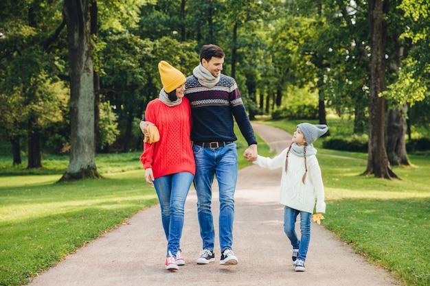 Het mooie paar omhelst elkaar, kijkt naar hun kleine knappe dochter, loopt door het groene park