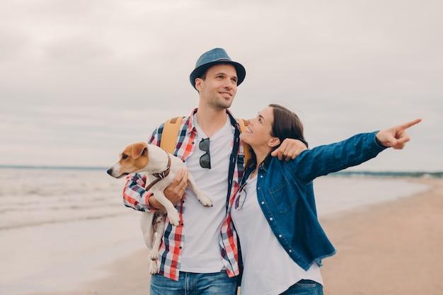 Het mooie paar omhelst en loopt buiten op zandstrand, draagt favoriete hond