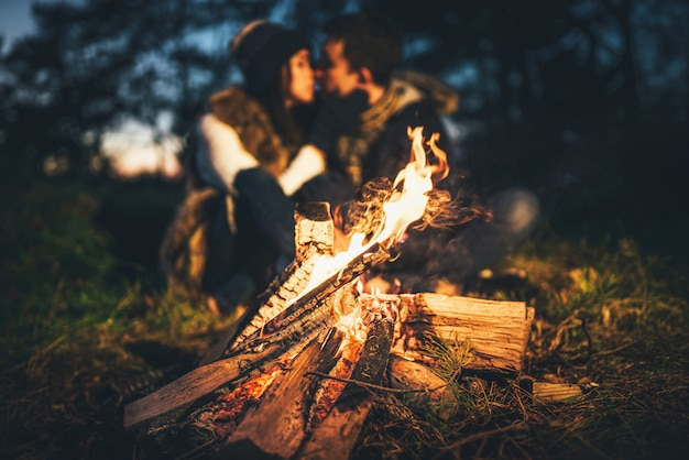 Het mooie paar ontspannen dichtbij vuur in het bos in avondtijd
