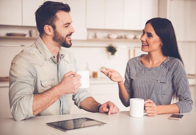 Het mooie paar spreekt, drinkt thee en glimlacht