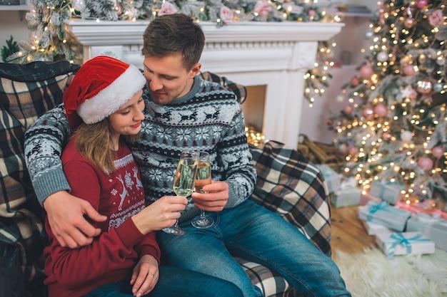 Het mooie paar zit samen en houdt glazen champaigne vast. jonge man omhelst vrouw. ze kijkt naar een bril. ze zitten in een ingerichte kamer.