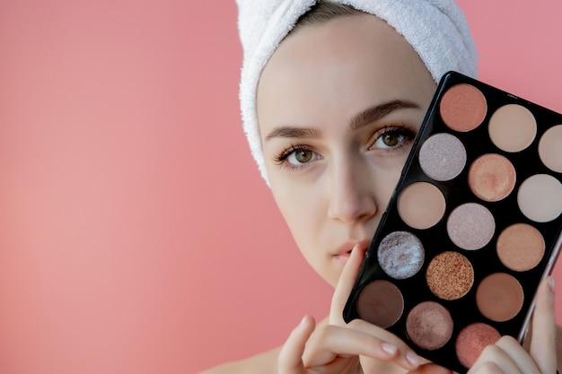 Het mooie palet van de vrouwenholding van kleurrijke oogschaduwwen op roze achtergrond. kopieer ruimte