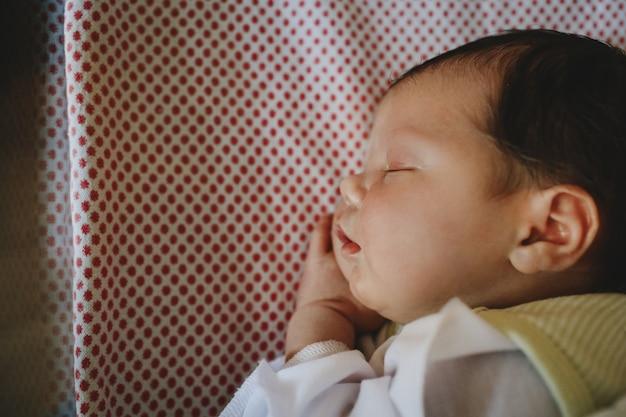 Het mooie pasgeboren kind ligt op een bed en slaap