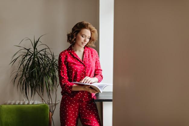 Het mooie peinzende tijdschrift van de vrouwenlezing in ochtend. binnen schot van aantrekkelijke vrouw in rode nachtkleding.