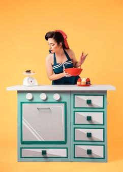 Het mooie pinupmeisje stellen in een keuken