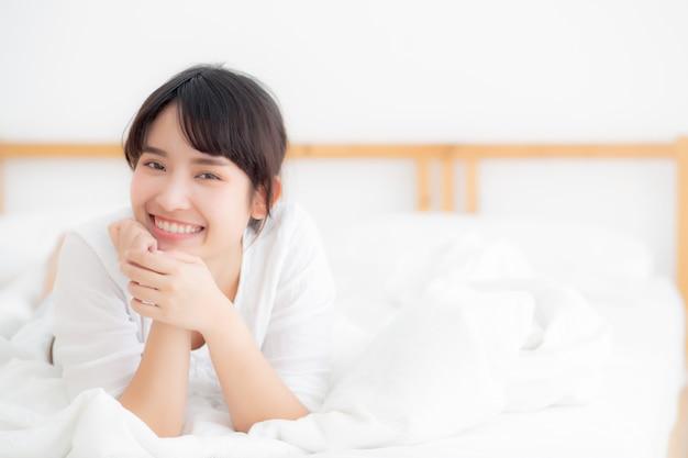 Het mooie portret jonge aziatische vrouw liggen en glimlach terwijl kielzog omhoog met zonsopgang bij ochtend