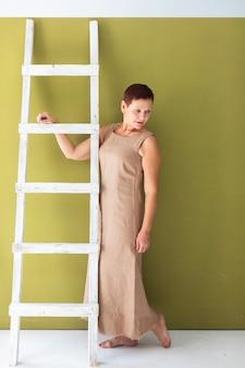 Het mooie rijpe vrouw stellen met ladder