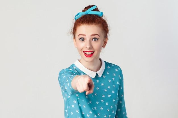Het mooie roodharige meisje, gekleed in een blauwe jurk, wijd open mond, verraste geschokte blikken, wijzende vinger naar de camera. geïsoleerde studio-opname op grijze achtergrond
