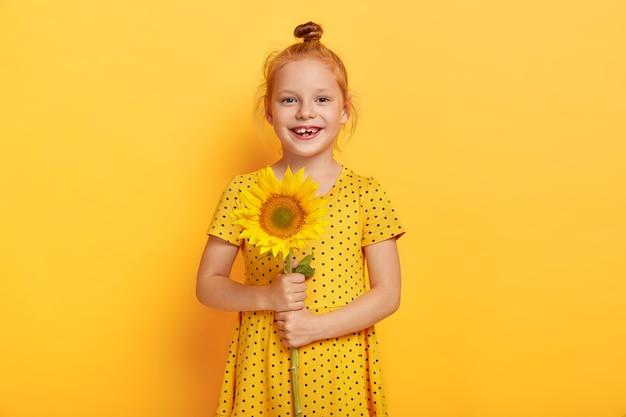 Het mooie roodharige meisje houdt zonnebloem