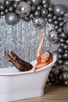 Het mooie roodharige meisje verheugt zich zittend gekleed in het bad. tegen klatergoud en ballonnen. succes concept.