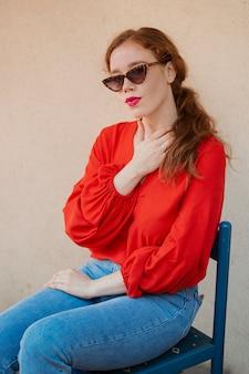 Het mooie roodharigevrouw stellen op een blauwe stoel