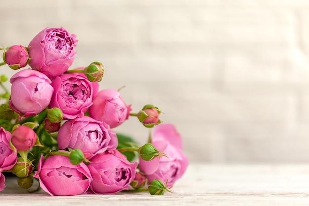 Het mooie roze boeket van bloemenrozen op witte muurachtergrond.