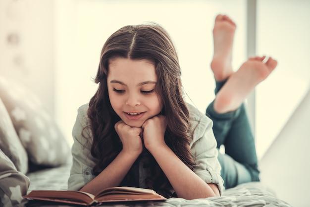 Het mooie schoolmeisje leest een boek en glimlacht.