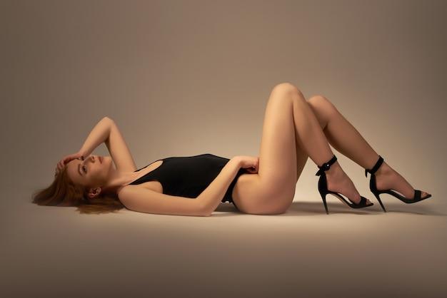 Het mooie, sexy, atletische blonde meisje ligt op de vloer.