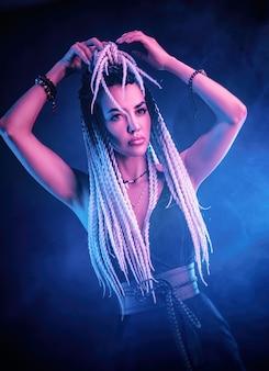 Het mooie sexy meisje met lange dreadlocks poseren in neonlicht